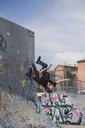 Tattooed man doing parkour in a skatepark - ACPF00083