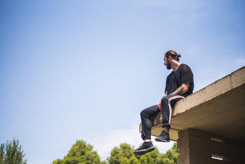 Tattooed man sittin on roof top - ACPF00092