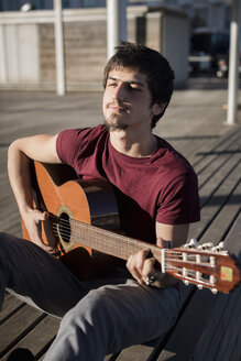 Young man sitting on a bench playing guitar - MAUF01447