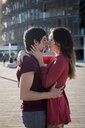 Affectionate young couple standing on city square - MAUF01453