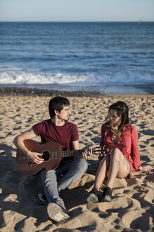 Couple with a guitar sitting on the beach - MAUF01459