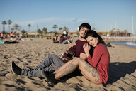 Spain, Barcelona, couple with a guitar sitting on the beach - MAUF01462