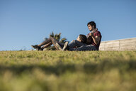 Young couple playing guitar on a meadow - MAUF01468