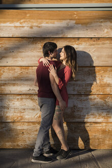 Affectionate young couple hugging at wooden wall - MAUF01474