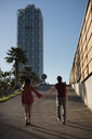 Spain, Barcelona, couple walking hand in hand  in the city - MAUF01477