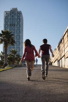 Spain, Barcelona, couple running hand in hand  in the city - MAUF01480