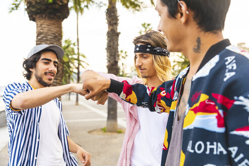 Multicultural group of three friends bumping fists - WPEF00657