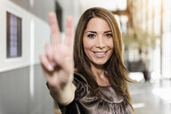 Portrait of mid adult businesswoman holding up hand in victory sign - ISF16531
