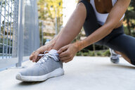 Close-up of sportive woman tying her shoes before workout - KKAF01154