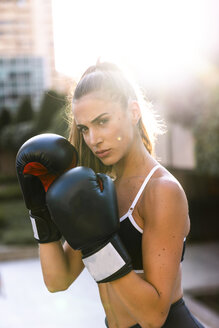 Portrait of sportive young woman boxing in the city - KKAF01157