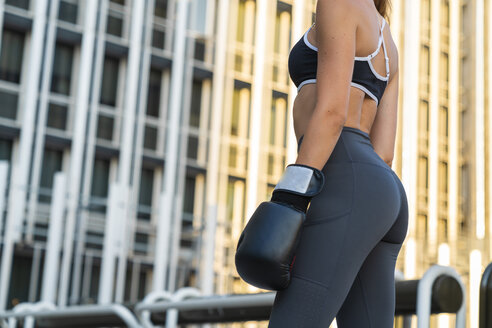 Sportive young woman with boxing gloves in the city in front of a high-rise building - KKAF01175