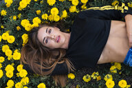 Portrait of attractive young woman lying in flower meadow - KKAF01187