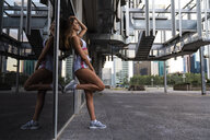 Attractive young woman in sportswear leaning against glass front of a building - KKAF01193