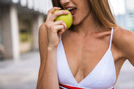 Close-up of young woman wearing sports bra eating an apple - KKAF01199