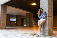 Attractive young woman in sportswear and denim jacket leaning against a column - KKAF01202