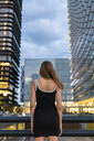 Rear view of young woman wearing black dress in the city at dusk - KKAF01211