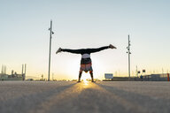 Acrobat doing handstand in the city at sunrise - AFVF00665