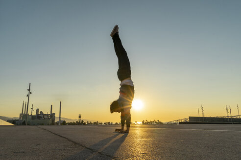 Acrobat doing handstand in the city at sunrise - AFVF00668