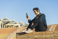 Man with headphones sitting on wood stack, using smartphone - AFVF00686