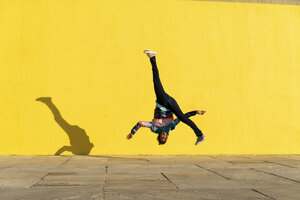 Acrobat jumping somersaults in front of yellow wall - AFVF00695