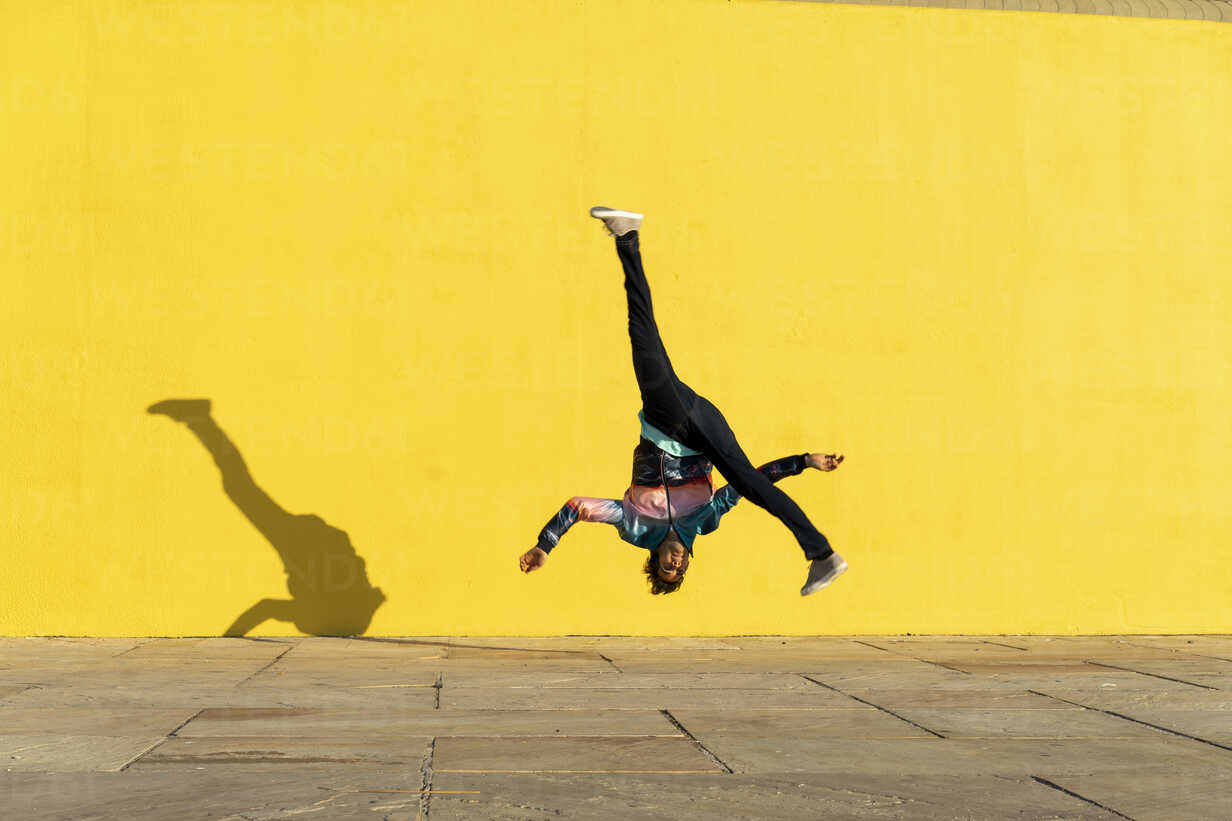 Acrobat jumping somersaults in front of yellow wall - AFVF00695 - VITTA GALLERY/Westend61
