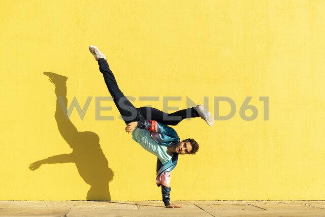 Acrobat doing movement training in front of a yellow wall - AFVF00698 - VITTA GALLERY/Westend61