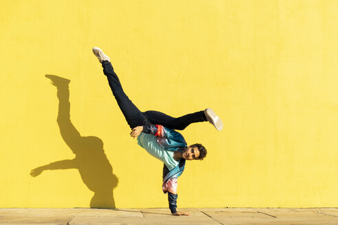 Acrobat doing movement training in front of a yellow wall - AFVF00698