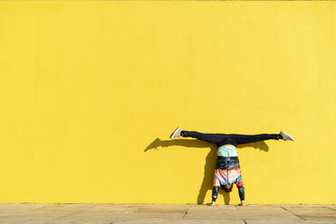 Acrobat doing handstand in front of a yellow wall - AFVF00701