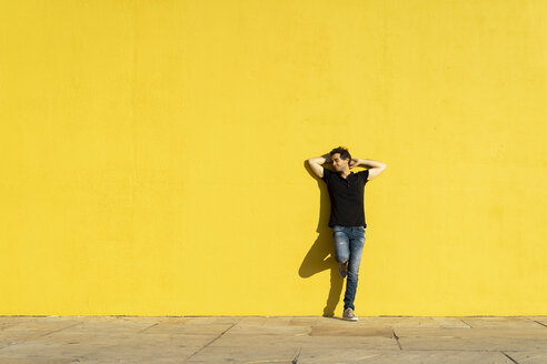 Man leaning against yellow wall with hands behind head - AFVF00704