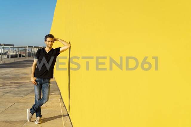 Man leaning against yellow wall, smiling, thinking - AFVF00707 - VITTA GALLERY/Westend61