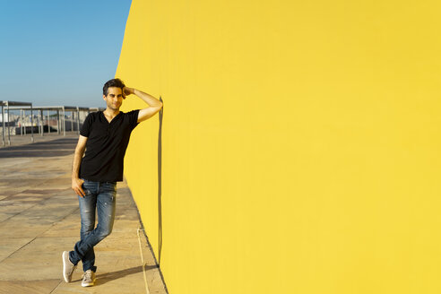 Man leaning against yellow wall, smiling, thinking - AFVF00707