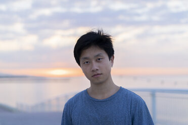 Young Chinese man at beach at sunrise, portrait - AFVF00713