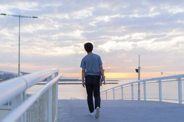 Young Chinese man with skateboard at the beach at sunrise - AFVF00716