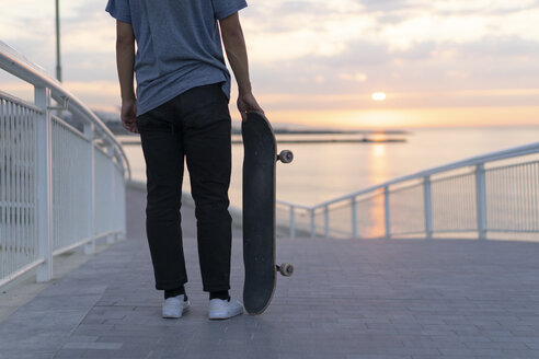 Young man with skateboard at the beach at sunrise, rear view - AFVF00719