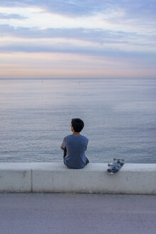 Young Chinese man with skateboard sitting on wall at the beach - AFVF00722