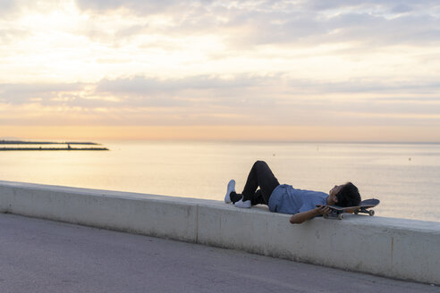 Young Chinese man with skateboard lying on wall at the beach - AFVF00725