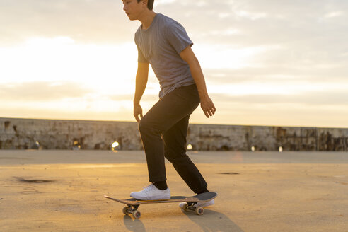 Young Chinese man skateboarding at sunsrise near the beach - AFVF00731