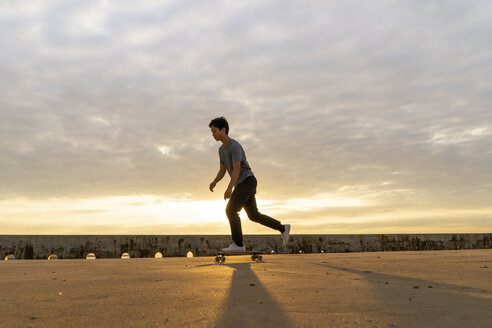 Young Chinese man skateboarding at sunsrise near the beach - AFVF00734