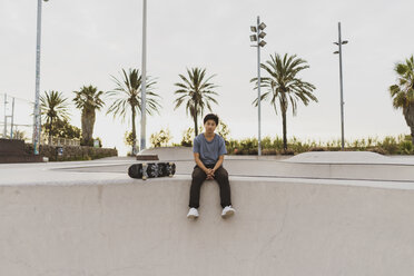 Young Chinese man sitting on wall of a skate park near the beach - AFVF00737
