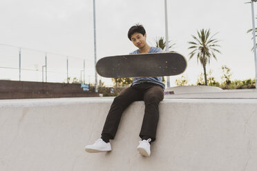 Young Chinese man sitting on wall of a skate park near the beach - AFVF00740