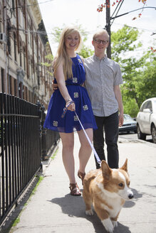 Young couple taking corgi dog for a walk along street - ISF16747