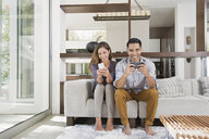 Couple playing games on smartphones on sitting room sofa - ISF16885