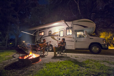 Mid adult couple and baby daughter sitting in front of campfire at night - ISF16891