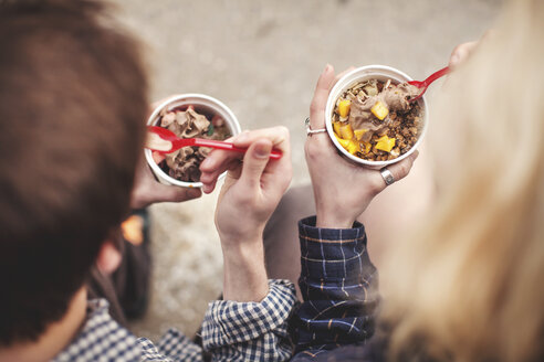 Couple eating tubs of frozen yoghurt treat - ISF16903
