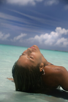 Woman laying on tropical beach - CUF39705