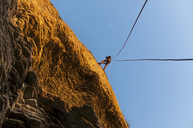Rock climber scaling steep rock face - CUF39759
