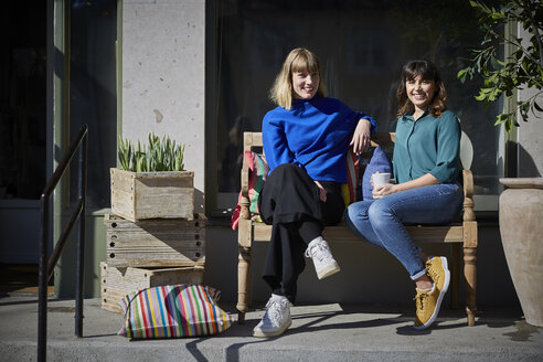 Full length portrait of smiling owners sitting on bench outside store - MASF08050