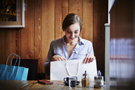 Young woman sitting in cafe looking in shopping bag - CUF39889