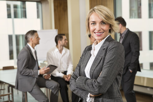 Businesswoman standing in front of colleagues - CUF39946