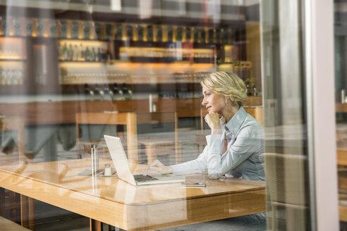 Businesswoman using laptop, view through window - CUF39949